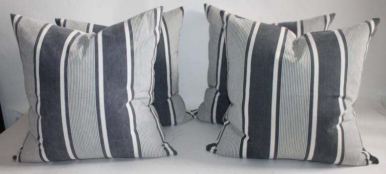 This group of four 19th century French black and white striped ticking pillows are in great as found condition. The faded black looks a little like grey in some lighting. The backing is in a white homespun linen. The inserts are down and feather