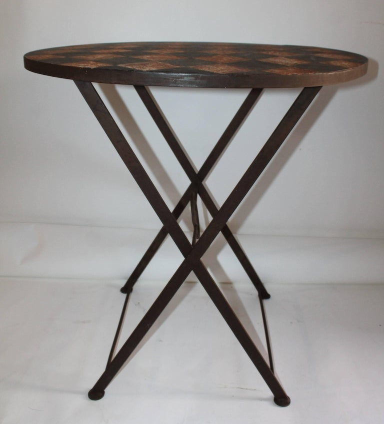 This folding painted iron garden or patio table has a checker board top and folding legs. The original painted top looks like a game board and has a wonderful patina.