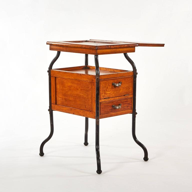 Unique early 20th century adjustable wood and steel side table with two drawers.