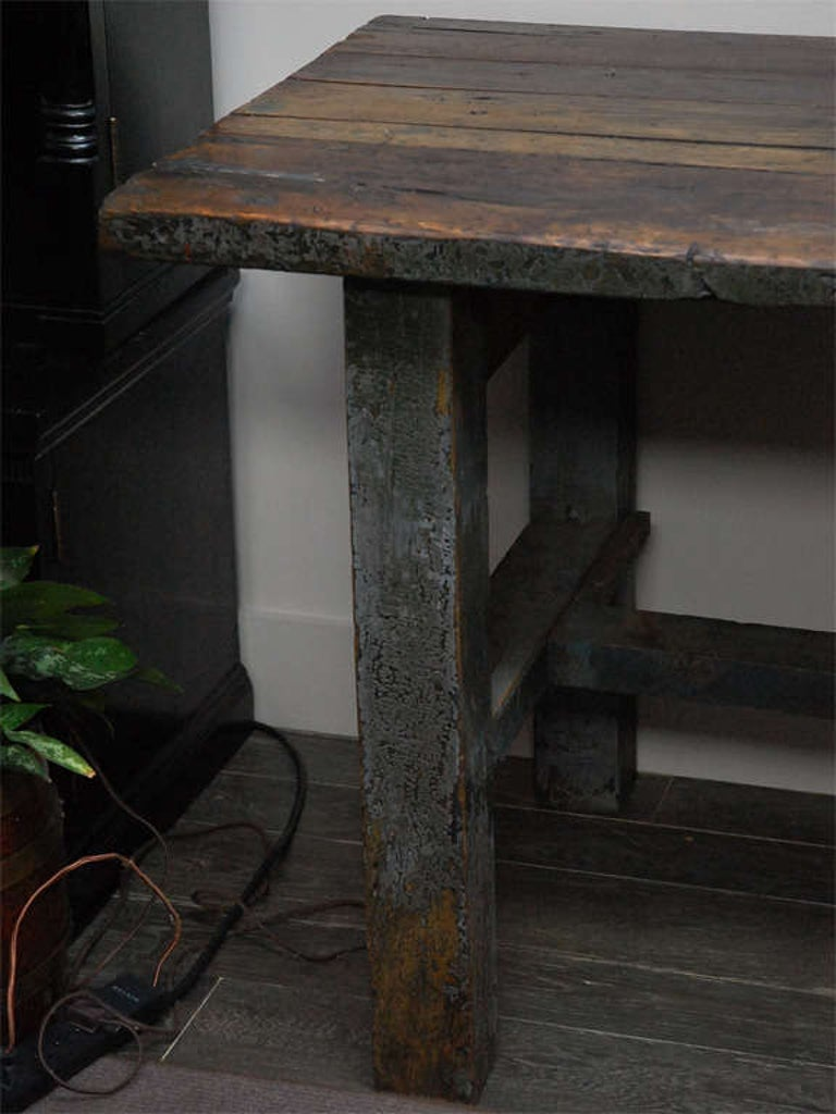 A rectangular wood plank top table with great antique character. The table has one drawer and straight legs joined by stretchers.