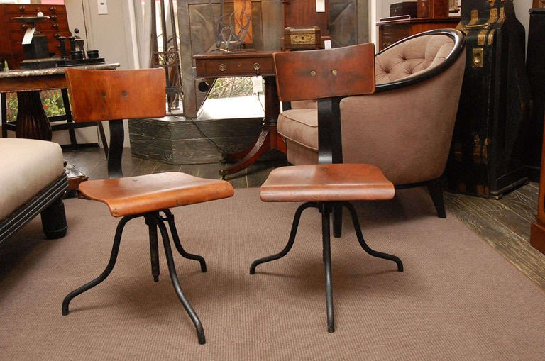 Wood and iron base swivel desk chairs with a curved wood back and adjustable curved seat over splayed iron legs.