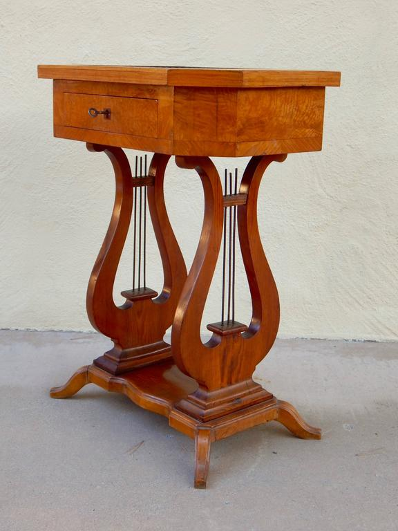 Swedish Art Deco Biedermeier revival lyre side table. Rendered in birchwood. Top in Carpathian elm with inlaid ebony and birch in sunburst inlay. One storage drawer with original kept, Sweden, circa 1920.