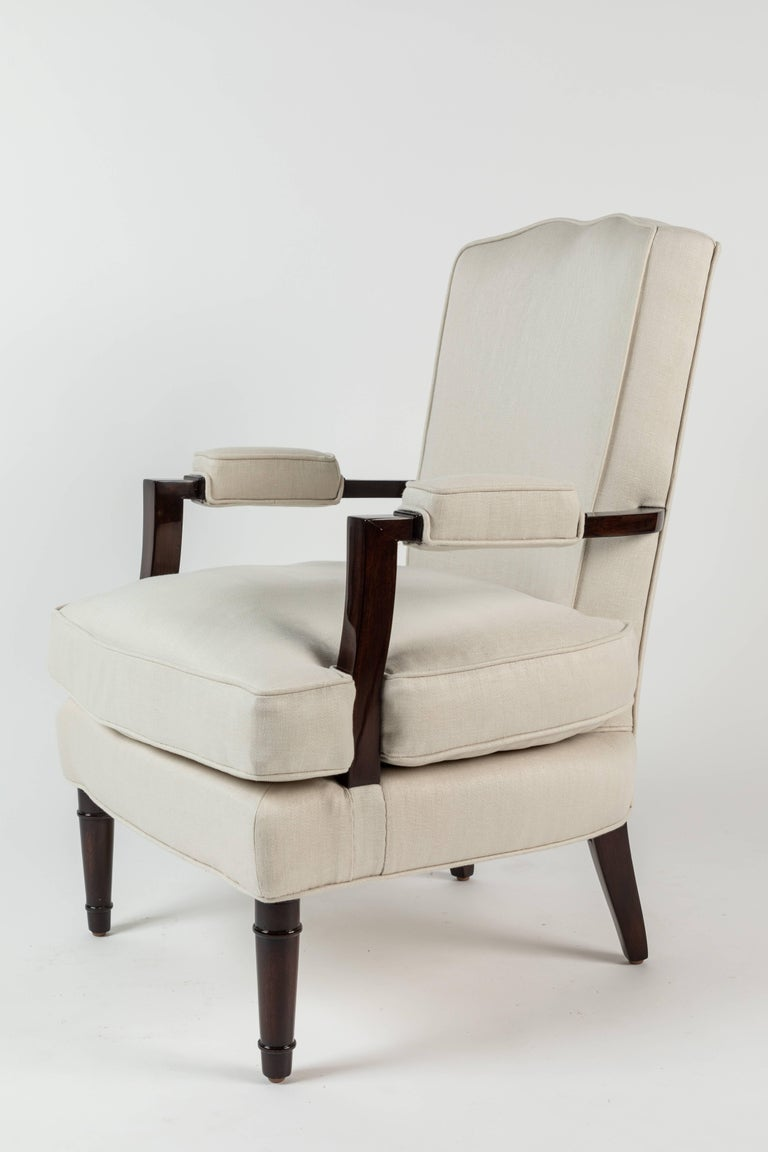 This stylish pair of armchairs designed by legendary designer and decorator Jules Leleu Reaganism their model number (25) 059 to the inside of the rear leg. Beautiful polished walnut frames and new Holland and Sherry linen upholstery, these chairs