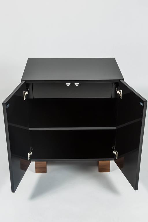 This chic cabinet in black lacquer studded with tigers eye cabochons and with walnut stained feet was designed by Patrick Dragonette for Dragonette Private Label. Featuring touch latch doors the cabinet houses a single drawer inside. This cabinet