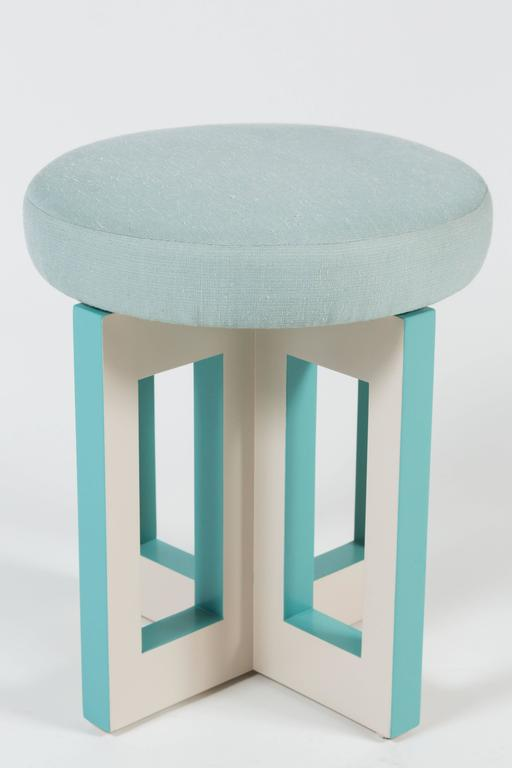 The Portola stool, a sophisticated swiveling occasional stool, features an upholstered seat atop a geometric inspired base, with both a lacquered and satin enamel finish. Shown in cream and blue, colors are fully customizable. This pair of stools is