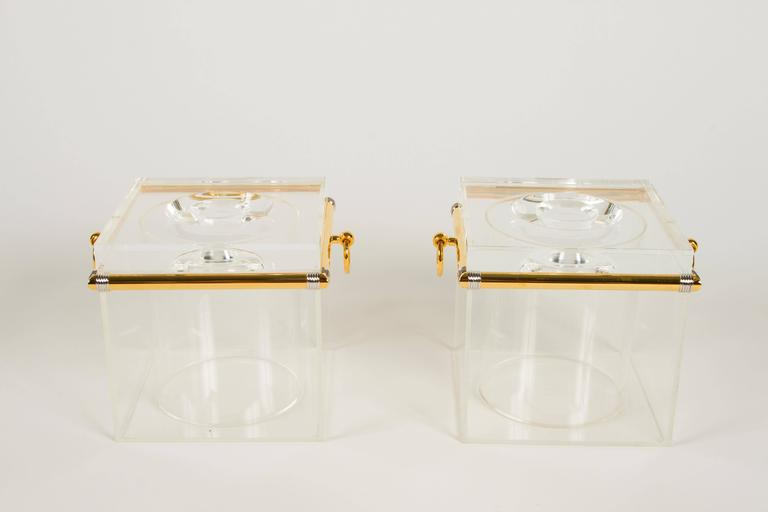 Uber chic pair of ice buckets no doubt of Italian origin. Fashioned from Lucite and finished with hardware in gold plate with contrast silver details at the corners. These buckets are high quality and totally stylish. There is on pair of gold plated