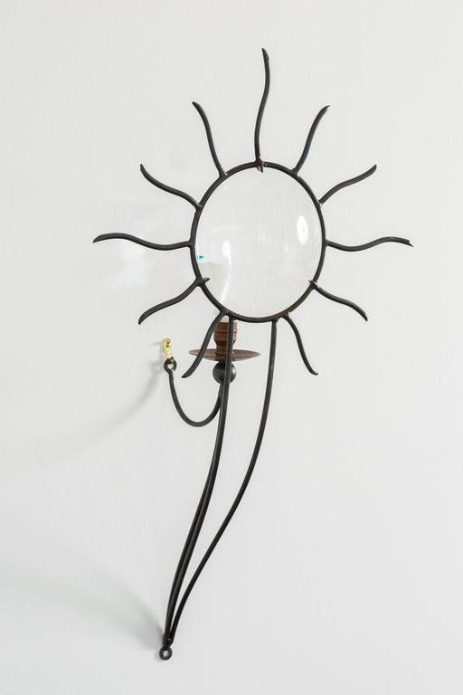 Late 20th century pair of thick-walled magnifying glass sconces in wrought iron forming a sunburst with brass socket and bobeche mounted on three supporting rods.` Designed 1992 by André Dubreuil (1951, French).