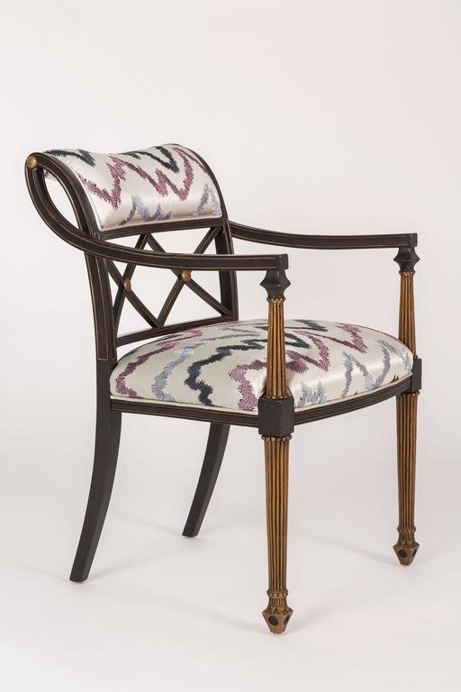 Chic and stylish set of six Regency style painted and gold leafed arm chairs. These chairs have been newly upholstered in Donghia's Hollywood fabric an embroidered satin. The finish is original and only the necessary touch ups were done. Interior