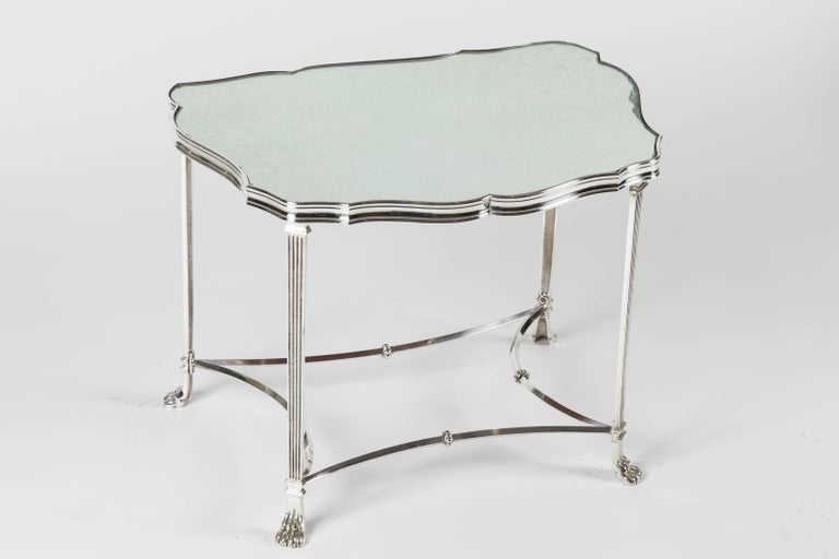 A beautiful pair of side tables with frames that terminate in claw feet and are finished in silver plate. Very reminiscent of Maison Jansen, the unusual shape is mirrored in the opposite table as they are a matched pair. The tables have