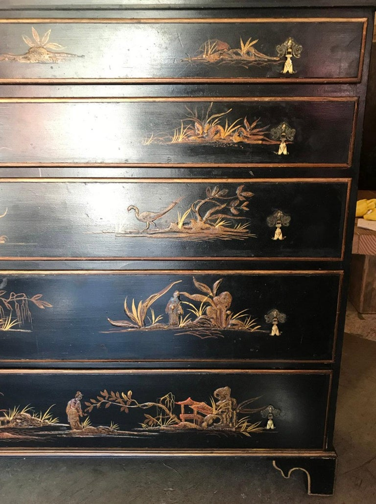 Unusual chinoiserie chest of drawers as it is only 13 inches deep. Five graduated drawers with raised decorated motives; pagodas, figures and nature, on a black and gilt background. Each painted scene is different. Interior of drawers are red.