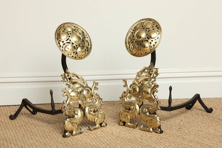 Striking and distinctive pair of English Arts and Crafts andirons, the pierced brass tops with embossed cabouchons over swan necks flanked by fire breathing griffins or wyverns bestride roundel embellished cartouches, with nicely worked wrought iron