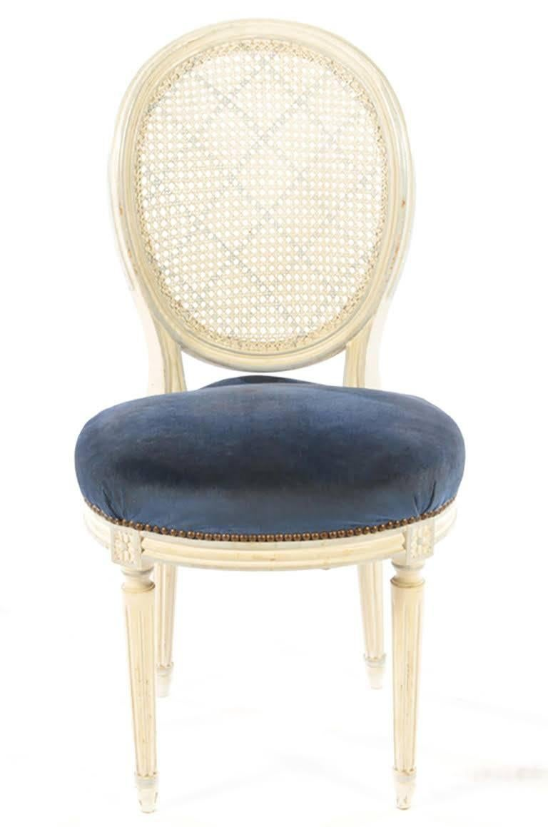 A set of eight painted balloon back dining chairs in the Louis XVI style with caned backs.