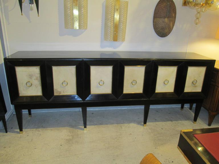 Ebonized sideboard with parchment doors and  brass banding on tapered legs ending in brass sabots. This sideboard measures 7 ft. 8 inches in length.