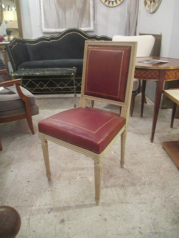 A set of four Louis XVI style leather-upholstered chairs, attributed to Maison Jansen.