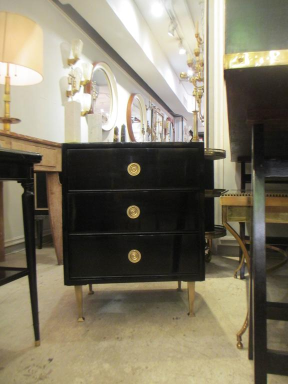 Pair of Mid-Century lacquered nightstands in the neoclassic manner on brass feet with three pull-out drawers.