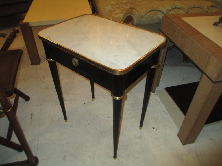 A pair of ebonized Jansen marble top end tables with central drawers  and bronze trimming on fluted tapered legs ending in brass sabots in the Louis XVI manner.