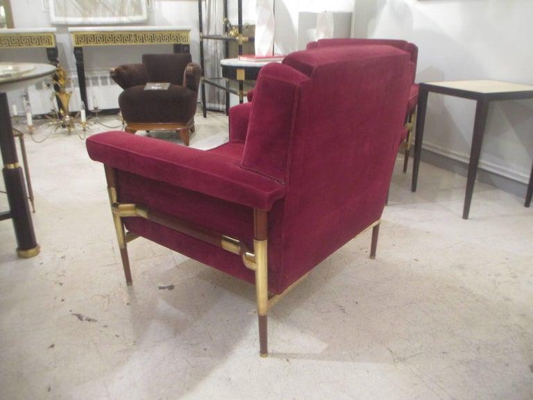 An unusual pair of brass-mounted midcentury Italian walnut lounge chairs.