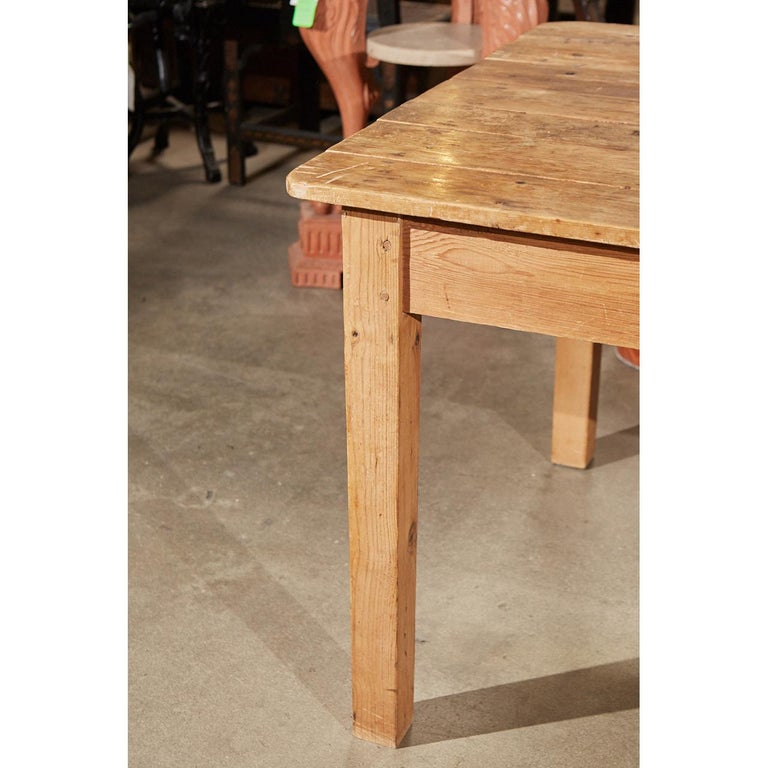 This country pine table is thought to be made in the late 19th or early 20th century in Ireland. The piece shows age and use with a well worn top and peg construction on the squared, gently tapered legs.