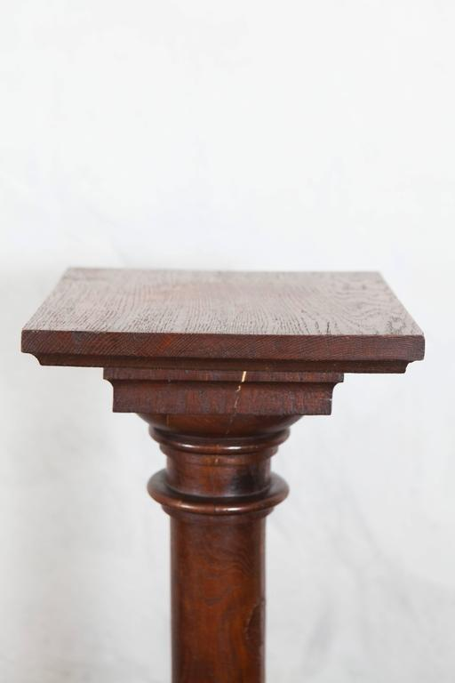 This attractive oak pedestal has a square top with nice delicate turned layers, rounded carved center piece and a stepped square base.