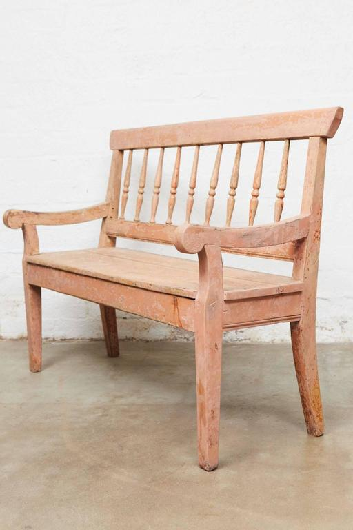 Spindle back bench for two with two arms on four square tapered legs, shaped arms and top rail. Once painted pinkish orange, surface shows fading, rubbing, losses as is usual with a distressed finish.