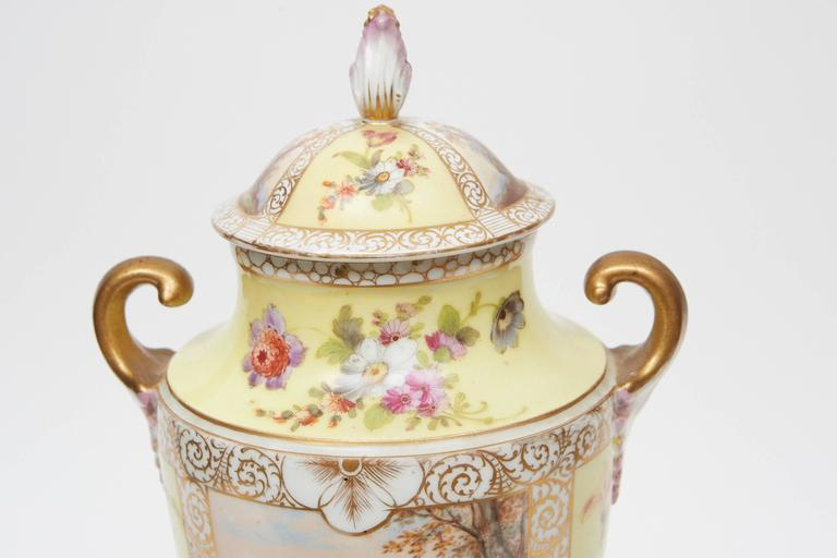 This Dresden hand-painted porcelain urn on plinth has floral and figurative elements throughout with two large scenes of couples on each side. The piece has gold painted decorative boarders and and two gold and rose hand-painted handles. The maker's