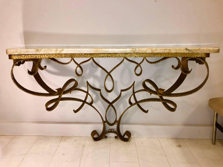 Hand-chaised and gilded ironwork in a flamboyantly elegant ribbon design, with breche Violette marble-top.