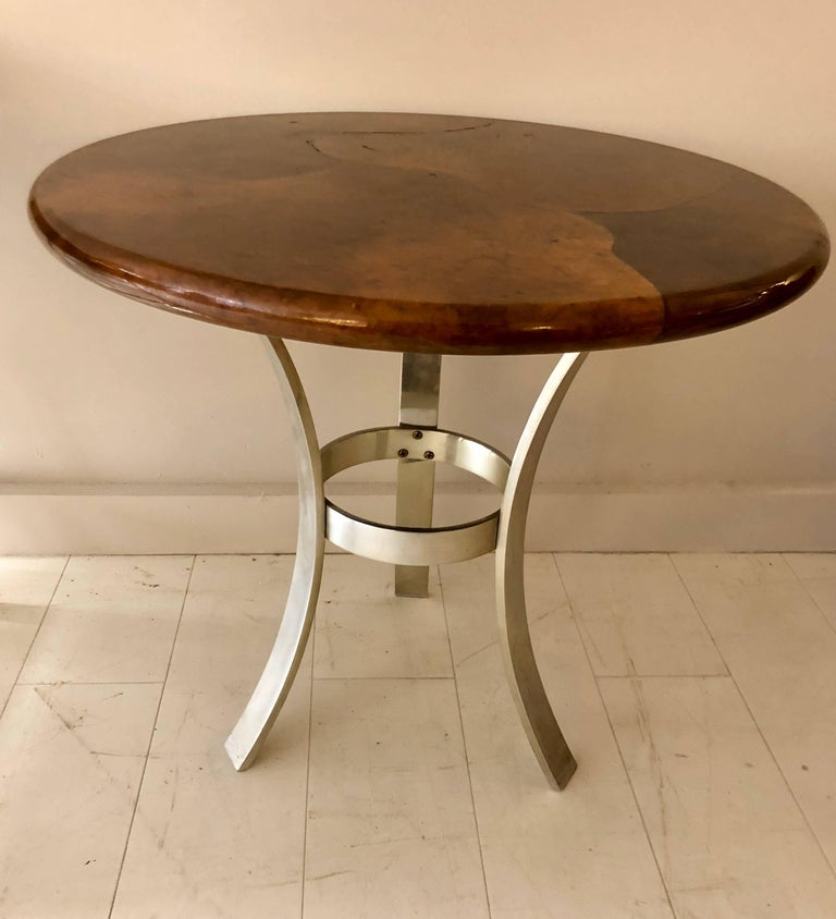 High quality 1970-1980s era table with brown parchment clad top on modernist tripod base. The form is after a John Vesey design and may be a later Paul M. Jones interpretation. Unsigned.