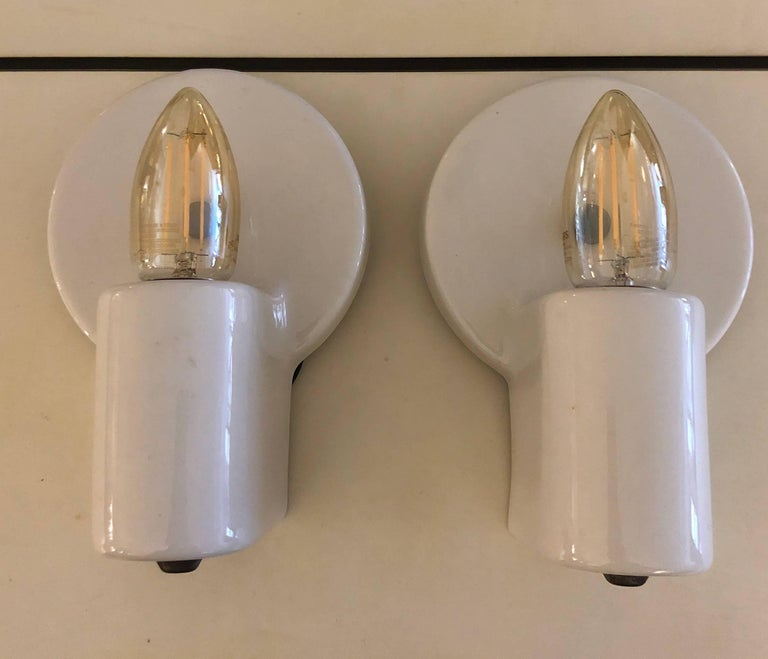 White porcelain wall lights designed by the great Swiss modernist architect. This pair is nicely minimalist, eschewing the usual pull chain, and embellished with the simplest brass tab hardware. For Pass & Seymour