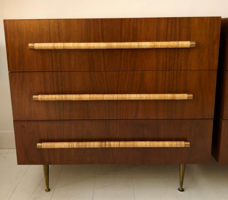 Pair of Classic T.H. Robsjohn-Gibbings for Widdicomb three-drawer cabinets in beautiful original finish dark walnut, with brass legs, and raffia cane wrapped handles. Signed with remnants of cloth Widdicomb label.