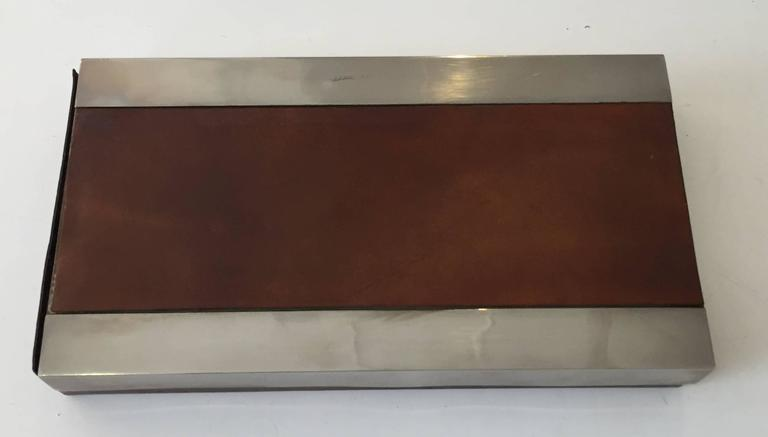 Chic leather box with steel accents. Top slides to reveal interior. Signed.