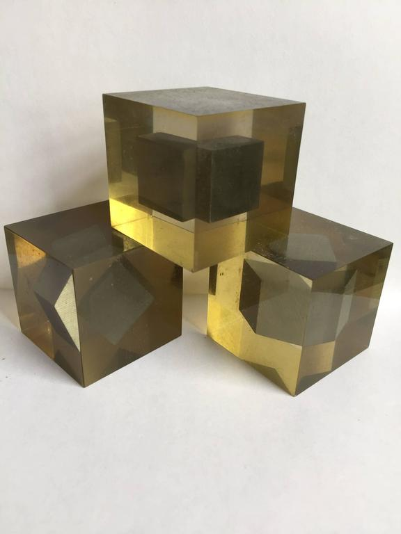 Three Lucite cubes each with a floating steel inclusion, from the Progressione di Tre series. For Danese.
