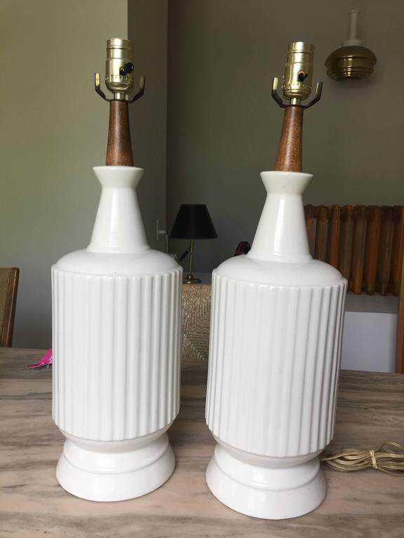 Handsome reeded drum blanc de chine table lamps with walnut neck and single socket. Unsigned but probably Italian pottery.  Lamps are 21