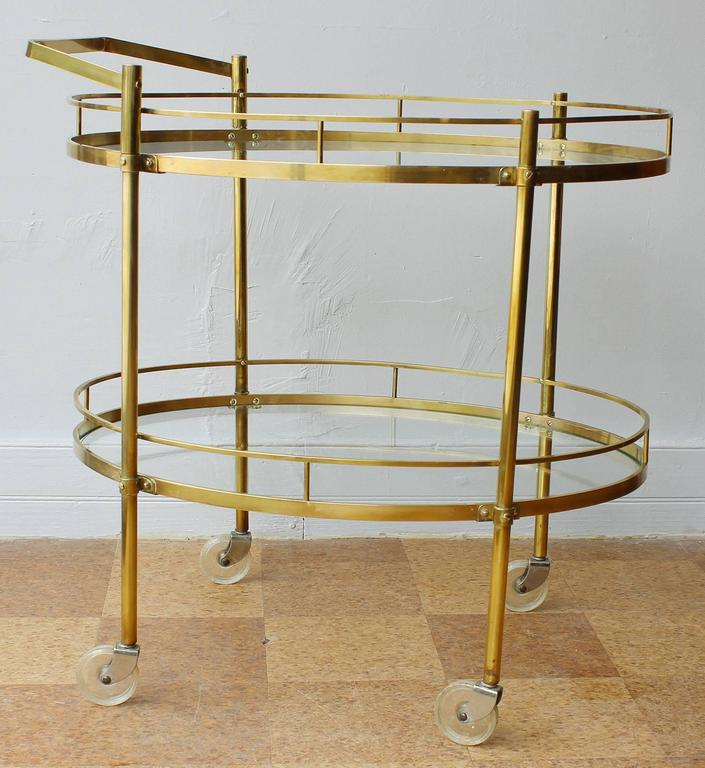 A 1960s two-tier solid brass server/ bar cart/ trolley with glass inserts and removable handle by Maxwell Phillips, NYC.