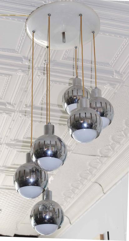 A vintage original Italian Mid-Century six drops pendant with chrome vented shades and enameled ceiling cap.