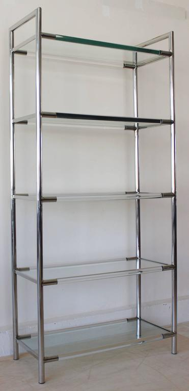 A handsome pair of Mid-Century chrome and Lucite etageres with tempered glass shelves in the manner of Charles Hollis Jones.