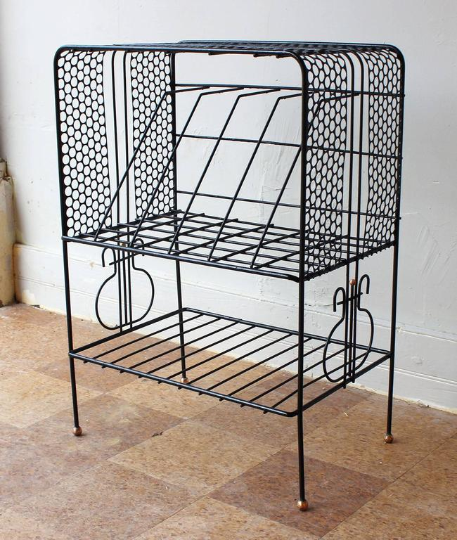 A charming Mategot style wrought iron record holder and magazine rack with brass foot details.