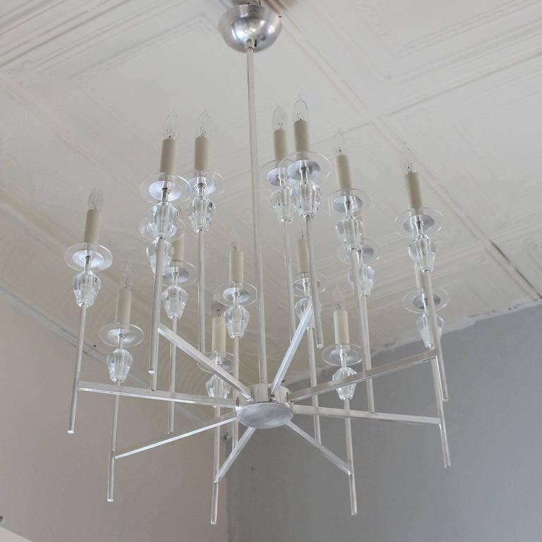 Elegant eight-arm silver plate chandelier with faceted Lucite crystals, in the manner of Tommi Parzinger.  Measures: Body height 20 inches.  Complementary delivery within 30 miles.