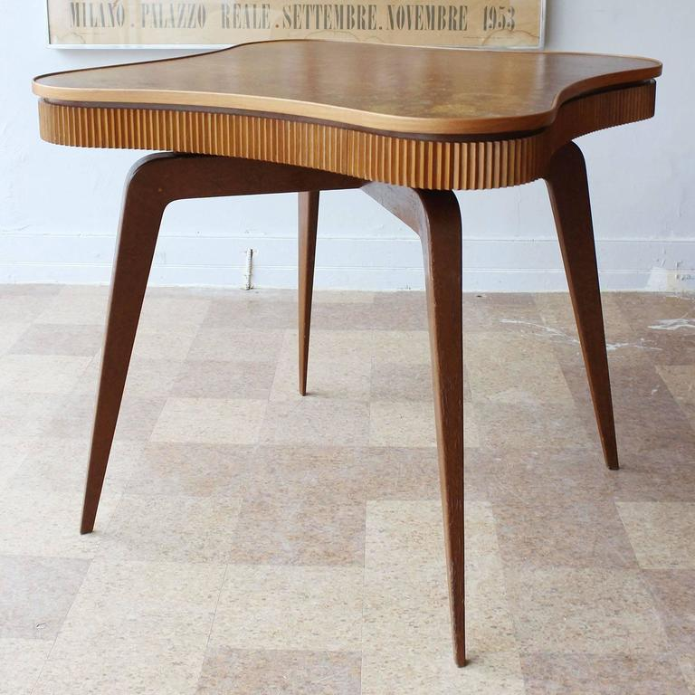 A Mid-Century wood game or dining table with four drawers and ribbed details in the manner of Paolo Buffa.
