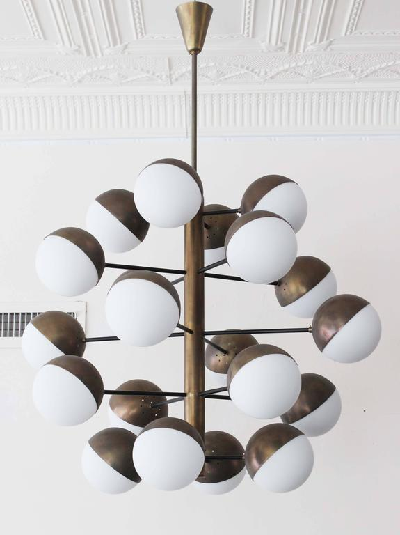A magnificent bronzed metal 20 globe stem Stilnovo style chandelier with milk glass.