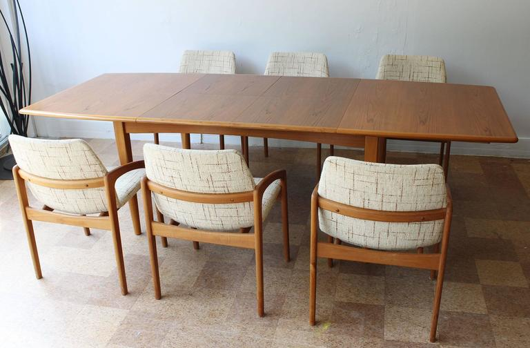 """An expandable teak dining table and six chairs by Kai Kristiansen, with two interior 19.5 inch leaves,  table opens to 101"""" wide  chairs.  Measures: 31"""" H (17.25"""" sh) x 21 W x 23 D."""