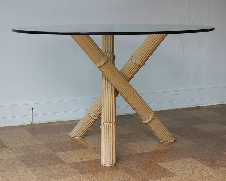 An Italian three-legged bamboo dining table with round glass top in vintage original condition.