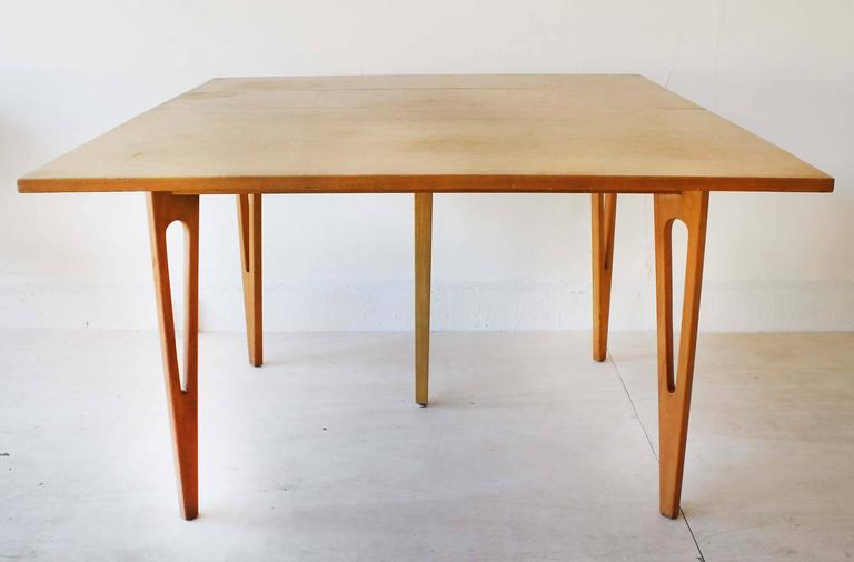 A Mid-Century fold-top maple wood table with three leaves, in the manner of Edmond Spence. Each leaf measures 11 x 41.5 inches. fully closed measures: 23.5 x 41.5 x 30.5H.