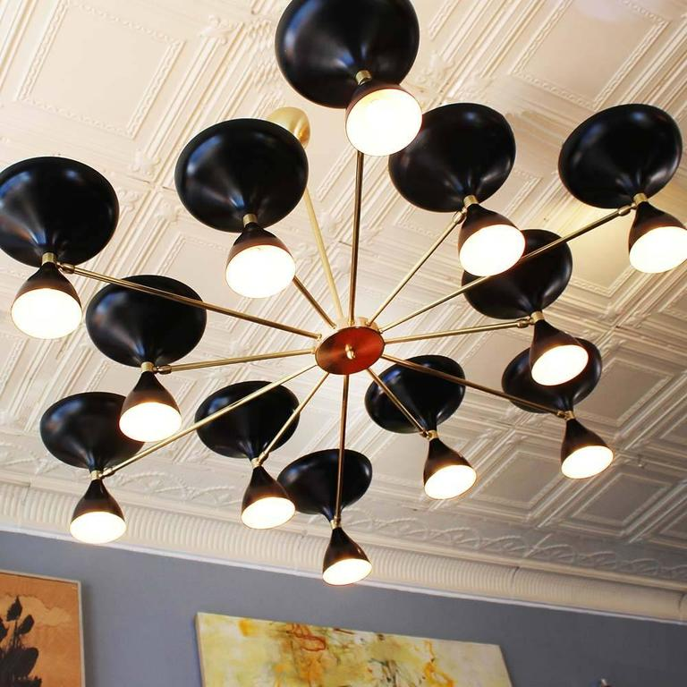 Our own exclusive sunburst design Milano chandelier, with 12 brass arms and pivoting powder coated heads with up and down sockets. In black or white, or both; nickel or brass; six-arm version also. All made in Italy.