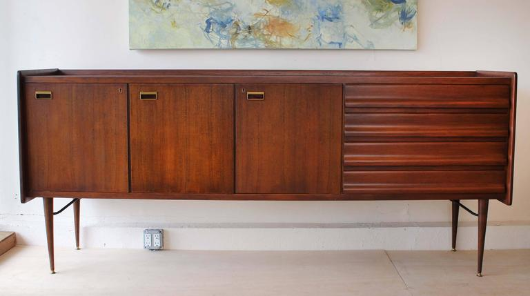 A handsome Mid-Century Italian wood sideboard with brass and enameled metal hardware.