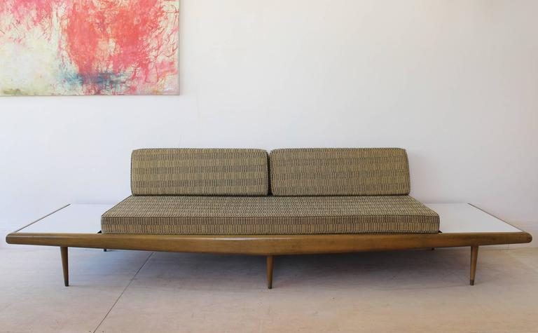 A walnut frame sofa daybed bench in the manner of Adrian Pearsall, with original cushions and bolsters, Formica and brass details.