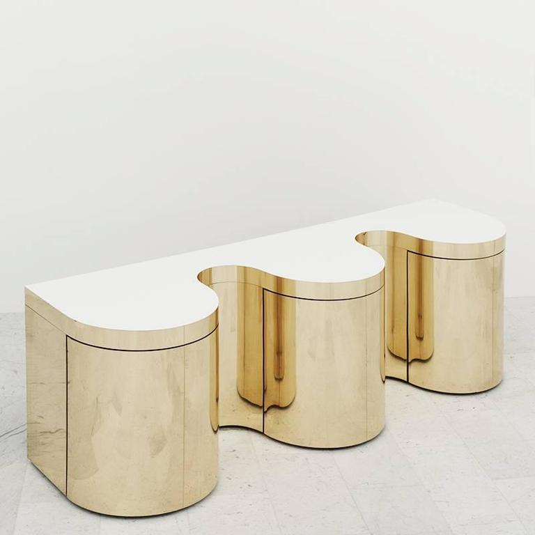A fantastic brass-plated steel undulating console designed by Paul Evans in the 1980s, this is one of the rare cylindrical examples from that era and is a final visual iteration of the artist's repertoire.  The console was one of the floor model