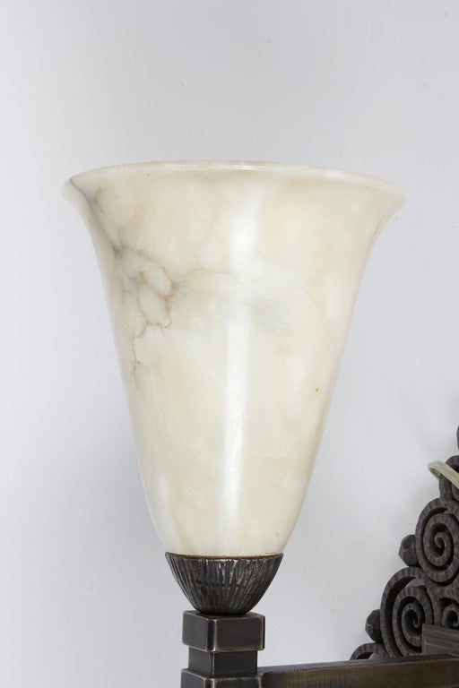 Edgar Brandt pair of wrought iron and alabaster wall sconces. Signed E. Brandt. Alabaster shades are old but may not be original.