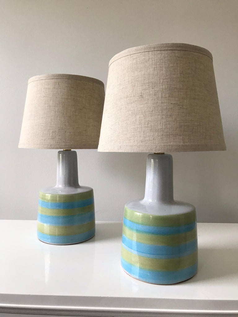 Wonderful pair of table lamps designed by Jane and Gordon Martz for Marshall Studios. Lamps feature thick white, green, and blue stripes. New shades, electrical components appear updated at some point.  Measures: Ceramic width 6.5
