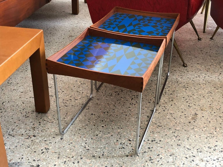 A matched pair of Norwegian enamel tray tables by Hermann Bongard for Plus, circa 1960s. Beautifully executed, removable tray tops in teak with dove tail joinery and an abstract enamel pattern. Legs collapse for easy shipping.