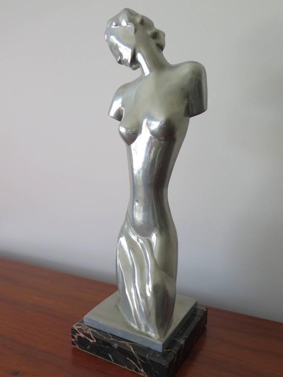 An unusual, stylized Art Deco statue of Aphrodite, goddess of love. Polished pewter on a marble base. Approximate 13.5